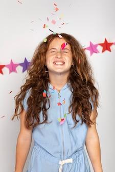 색종이와 중간 샷 웃는 소녀