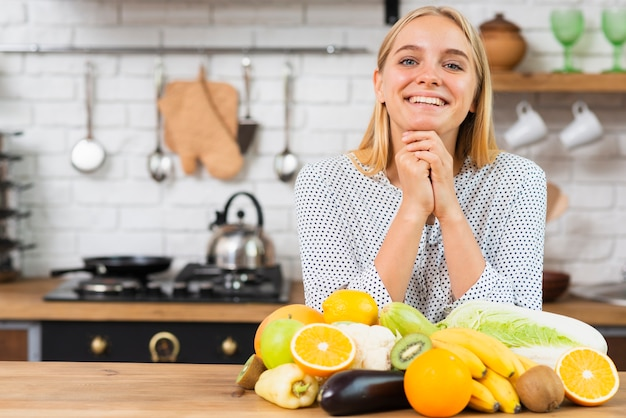Medium shot smiley girl with fruits in the kitchen