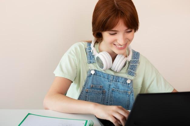 Medium shot smiley girl with laptop