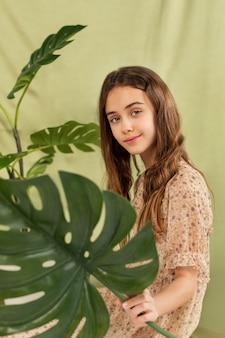 モンステラ植物とミディアムショットのスマイリーガール