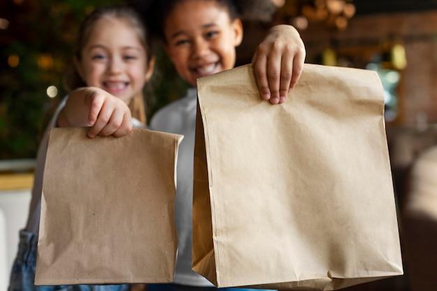 紙袋を持っているミディアムショットのスマイリーガール
