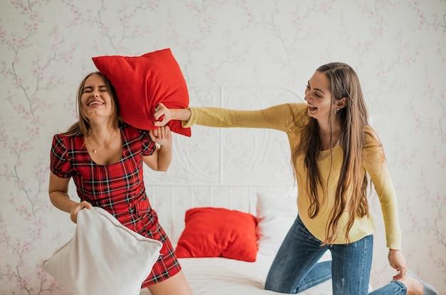 Medium shot smiley girls in a pillow fight