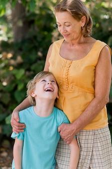 Medium shot smiley grandma looking at kid