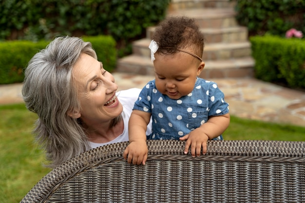 赤ちゃんを抱いてミディアムショットのスマイリー祖母