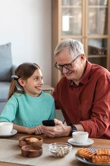 Medium shot smiley grandpa and girl