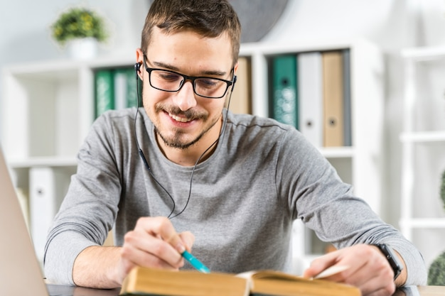 Medium shot smiley guy studying with headphones