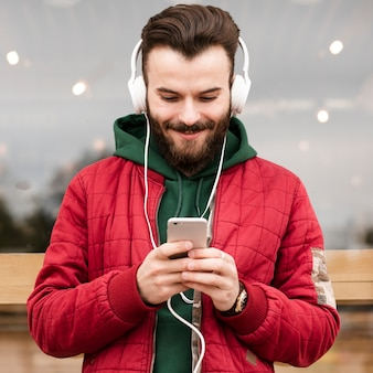Medium shot smiley guy with headphones looking at smartphone