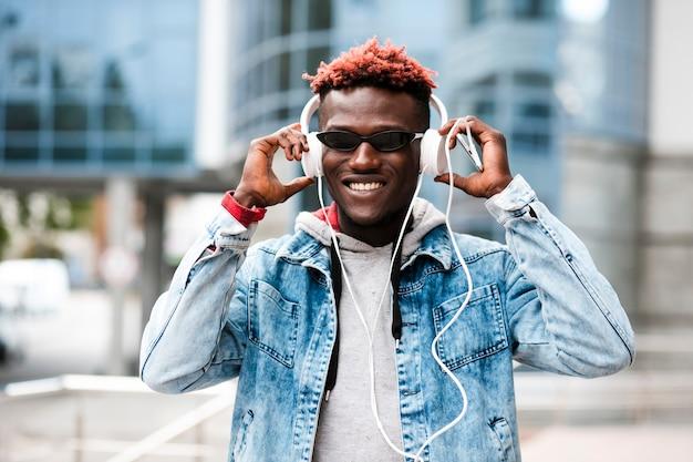Medium shot smiley guy with headphones and sunglasses