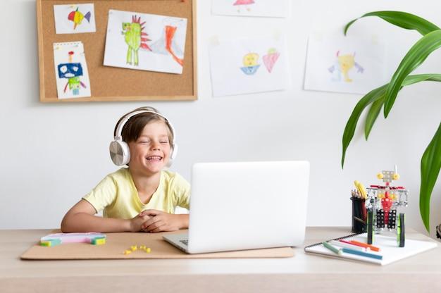 Средний снимок улыбающегося ребенка, смотрящего на ноутбук