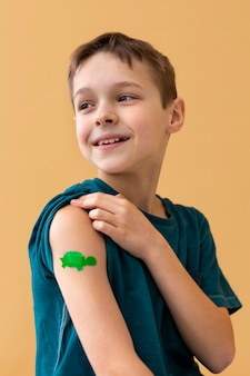 Medium shot smiley kid wearing band aid