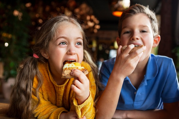 중간 샷 웃는 아이들이 피자를 먹고