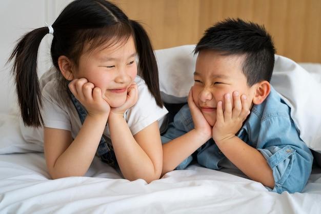 침대에서 중간 샷 웃는 아이