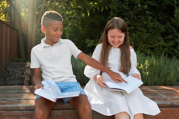 야외에서 독서를 하는 중간 샷 웃는 아이들