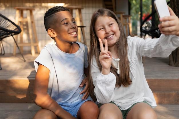 셀카를 찍는 중간 샷 웃는 아이들