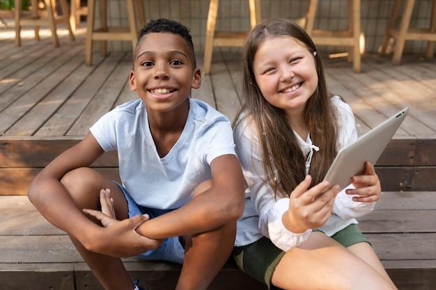 태블릿과 중간 샷 웃는 아이