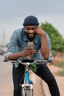 Uomo di smiley colpo medio sulla bicicletta con il telefono