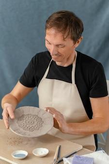 Uomo di smiley del colpo medio che fa ceramiche