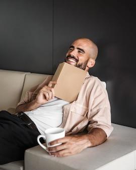 Medium shot smiley man holding book