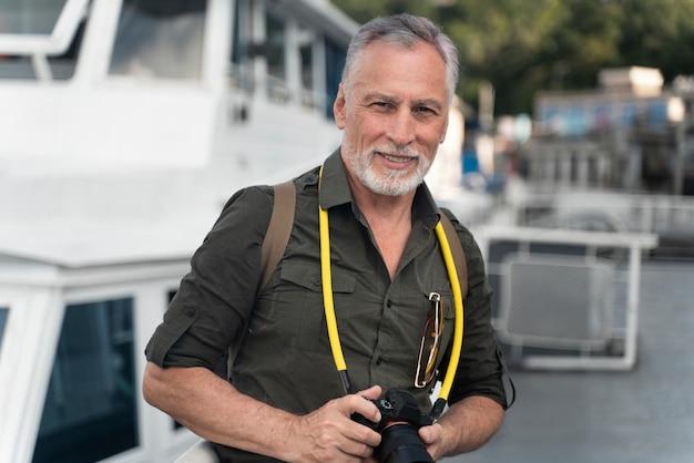 Uomo sorridente con colpo medio che tiene la macchina fotografica