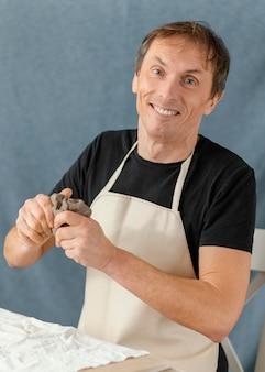 Uomo di smiley del colpo medio che tiene argilla