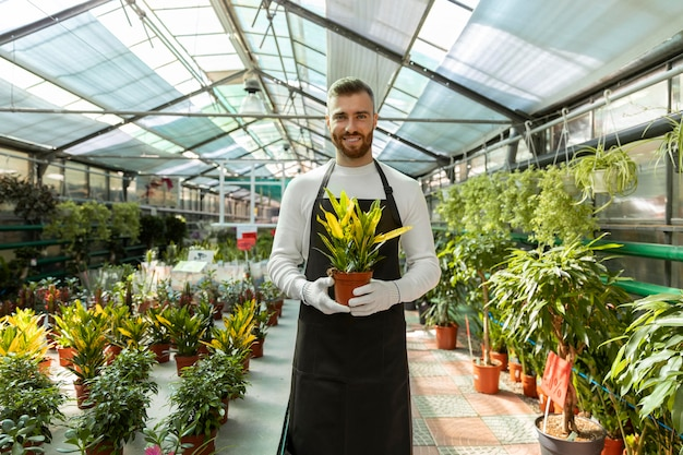 중간 샷 웃는 남자 들고 식물