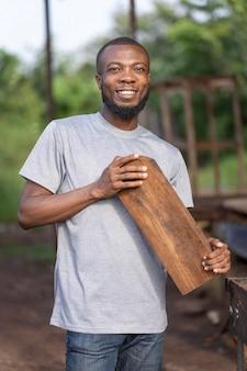 Medium shot smiley man holding wooden plank