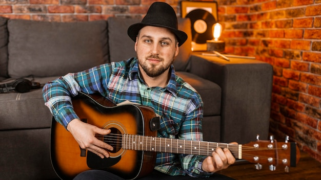Uomo di smiley del colpo medio che gioca chitarra