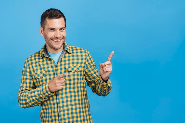 Medium shot smiley man pointing with copy space
