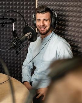 Medium shot smiley man at radio