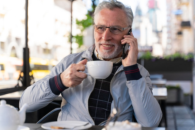 Улыбающийся человек среднего выстрела разговаривает по телефону