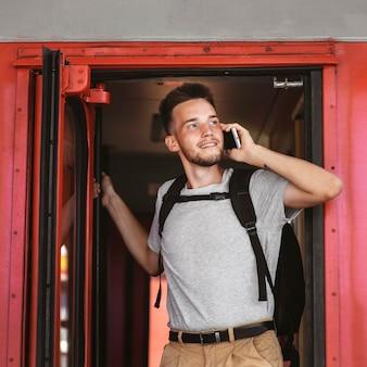 Uomo di smiley del colpo medio che parla sul telefono