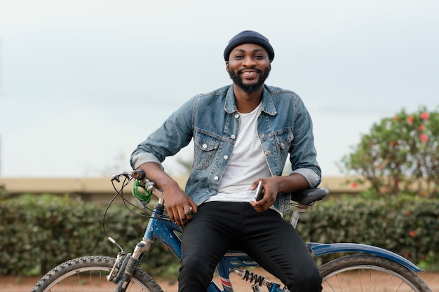 자연 속에서 자전거와 함께 중간 샷 웃는 남자