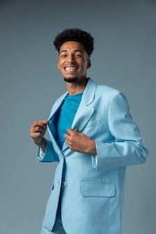 青い光沢のあるジャケットとミディアムショットのスマイリーマン