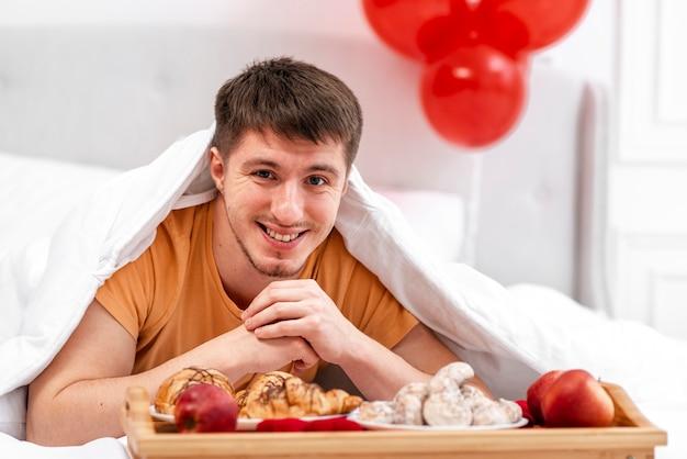 ベッドでの朝食とミディアムショットスマイリー男