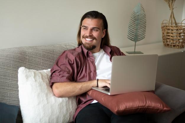 ノートパソコンでミディアムショットのスマイリー男