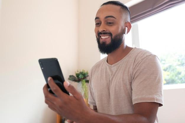 Uomo di smiley colpo medio con il telefono