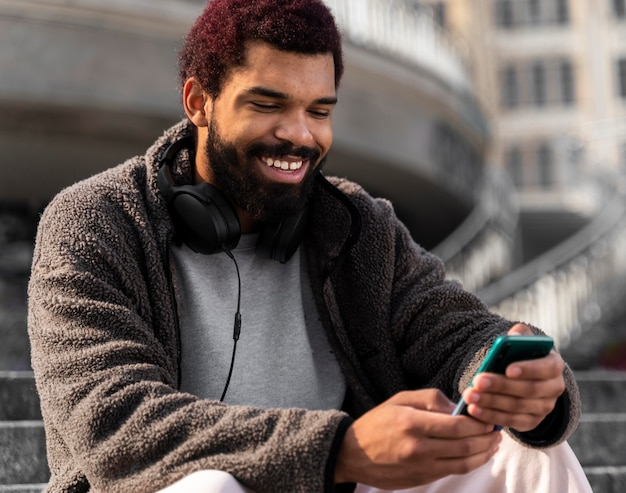 Medium shot smiley man with smartphone