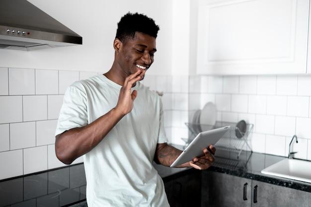 Uomo sorridente di colpo medio con tablet in cucina