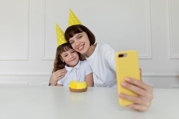 Medium shot smiley mother and girl taking selfies