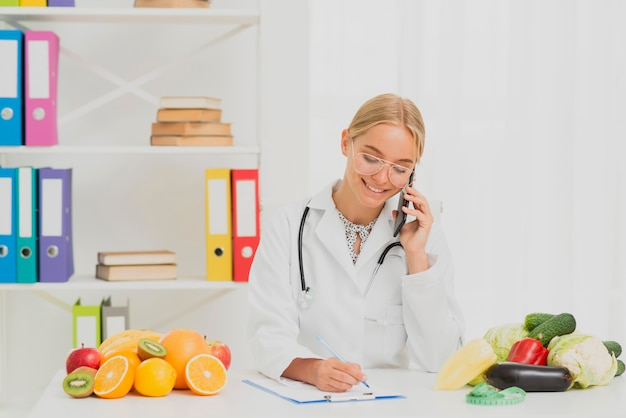 Medium shot smiley nutritionist talking on the phone