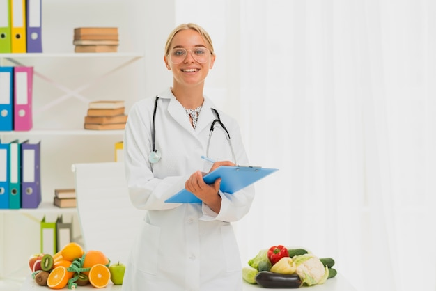 Medium shot smiley nutritionist with stethoscope