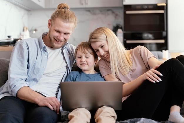 중간 샷 웃는 부모와 아이 노트북
