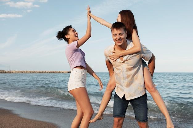 해변에서 중간 샷 웃는 사람들