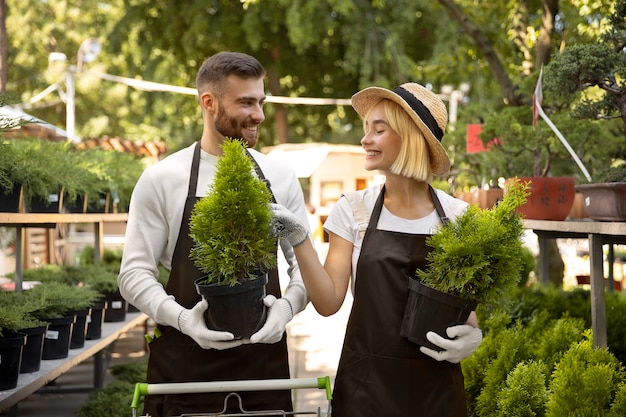 식물을 들고 중간 샷 웃는 사람들