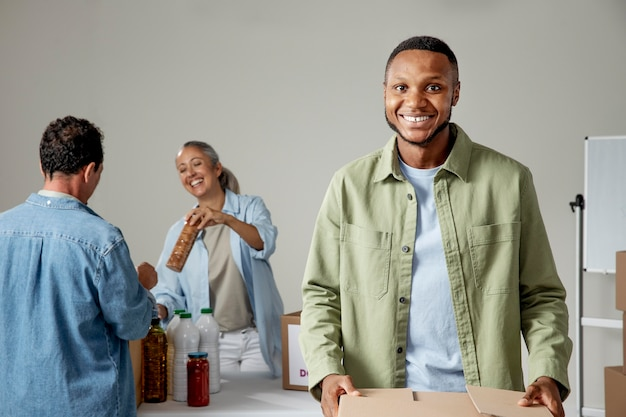 Persone sorridenti di piano medio che donano cibo
