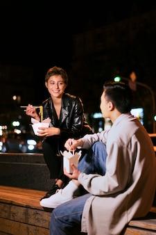 Persone sorridenti a colpo medio che mangiano insieme