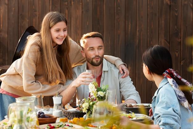 중간 샷 웃는 사람들이 테이블에 앉아