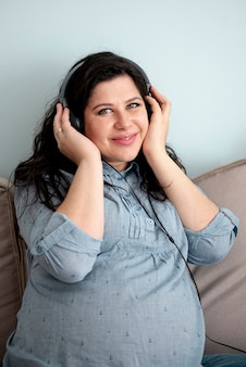 Medium shot smiley pregnant woman with headphones