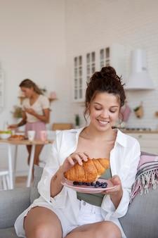 Улыбающиеся соседи по комнате среднего размера с едой