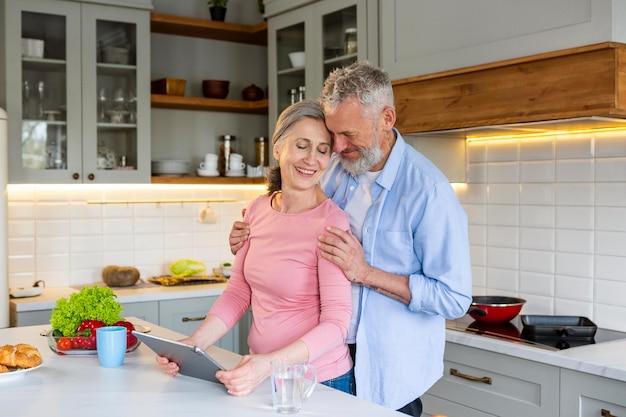Пара среднего возраста смайлик с планшетом